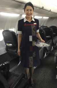 ニュース画像 2枚目:オリジナル大島紬エプロンを着用する客室乗務員