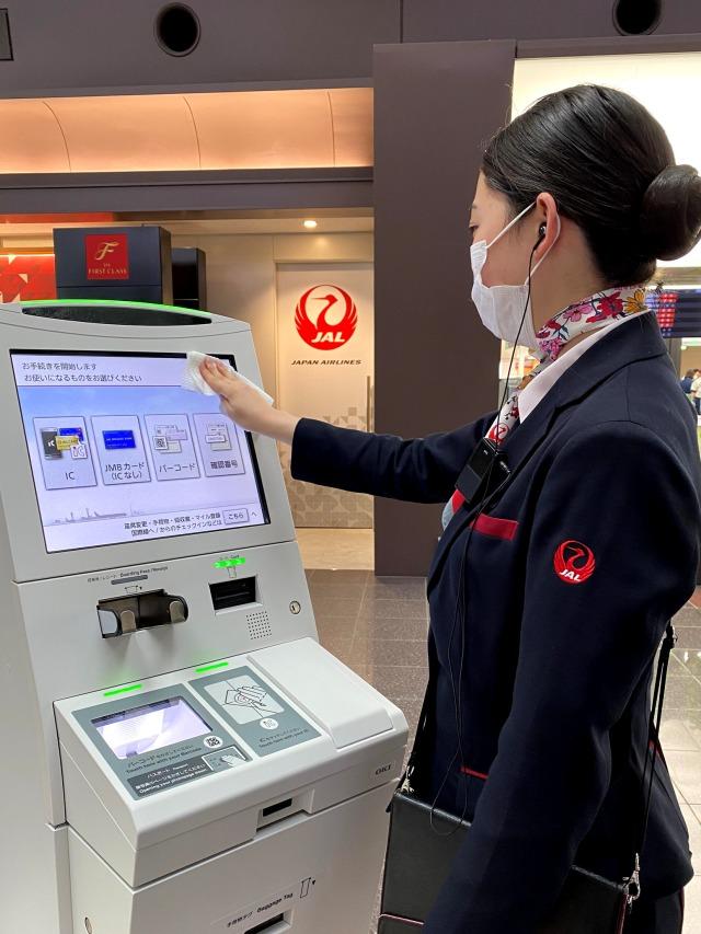 ニュース画像 1枚目:自動チェックイン機の消毒の様子