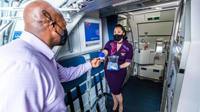 ニュース画像 1枚目:コロナ禍で手指消毒剤を乗客に手渡すデルタ航空の客室乗務員