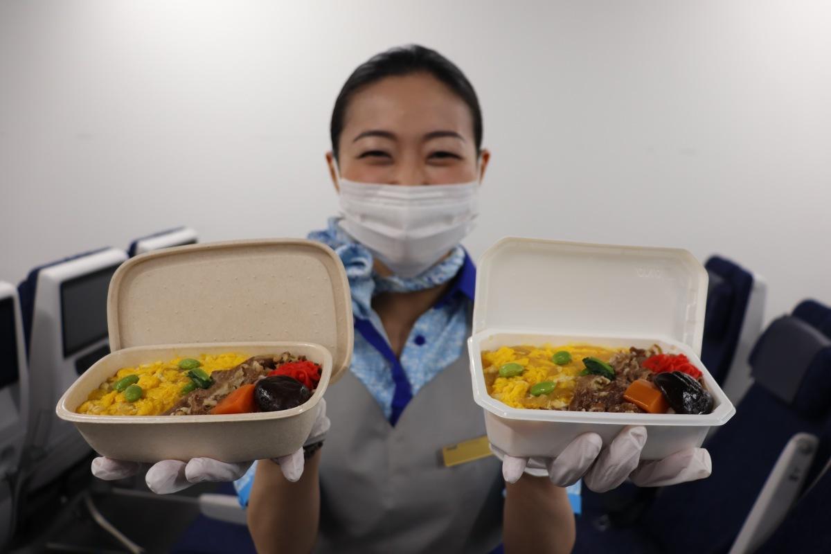 ニュース画像 1枚目:機内食容器、左がバガス素材、右が従来の容器