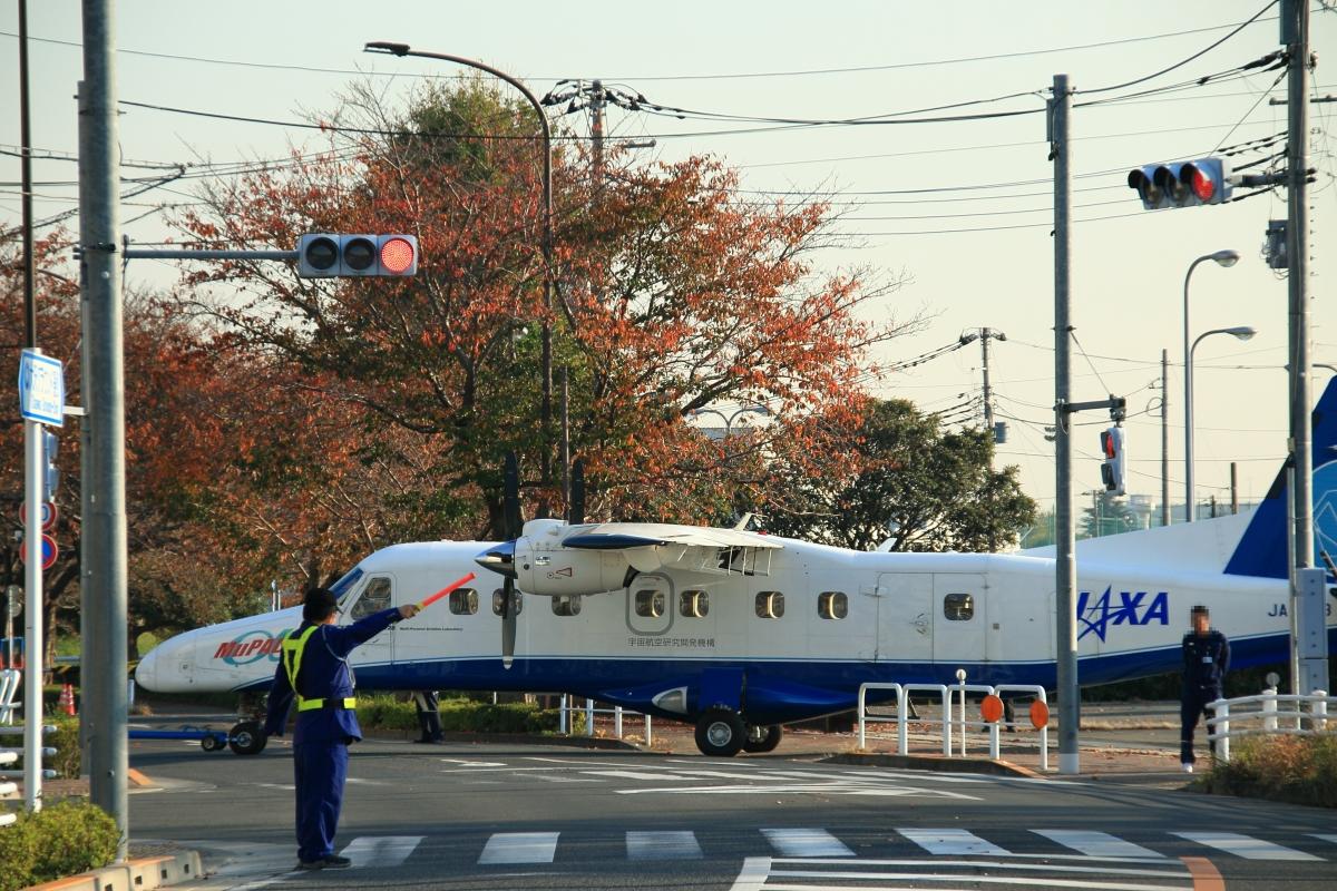 ニュース画像 1枚目:JAXA格納庫と調布飛行場の間の一般道横断は名物だった (だびでさん、2018年撮影)