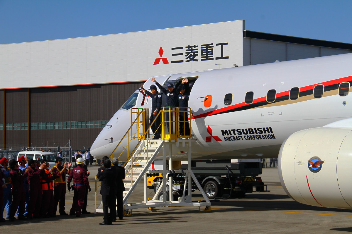 ニュース画像 1枚目:MRJ、JA21MJの初飛行を終え、手を振って機外に出てくる安村機長(中央)と戸田副機長(左)